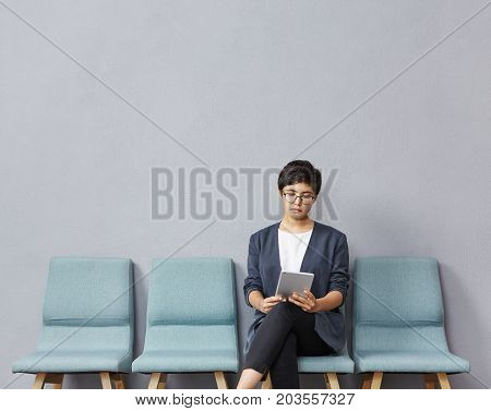 People, Technology And Occupation Concept. Beautiful Young Unemployed Woman Wearing Glasses Sitting