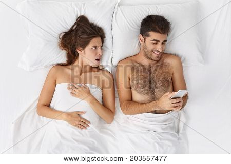 Jealous Beautiful Young Wife Has Angry Expression Looks At Man Who Recieves Message From Unknown Per