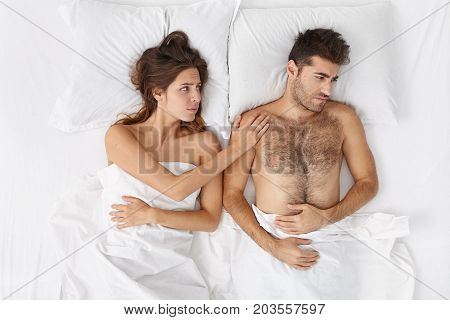 Attractive Female Cheering Up Her Anxious Man In Bed. Bearded Caucasian Male Feeling Frustrated Becu