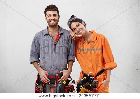 Portrait Of Team Of Cheerful Young Caucasian Male And Female Maintenance Workers Wearing Work Clothe