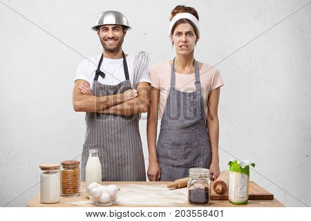 Annoyed Female Cooker Being Tired Of Her Work, Standing Near Her Companion Who Has Good Mood, Posing