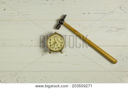 Hammer Pounding Old Style Alarm Clock on wooden background