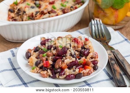Baked casserole with different kinds of beans rice and cheese on white plate and in ceramic baking dish horizontal