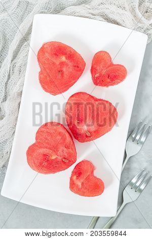 Slices of fresh seedless watermelon cut into heart shape on a white plate flat lay vertical