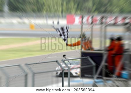 Blurry Of Man Holding And Waving The Flag On Stand For The Race At The Finish Line And Raceway
