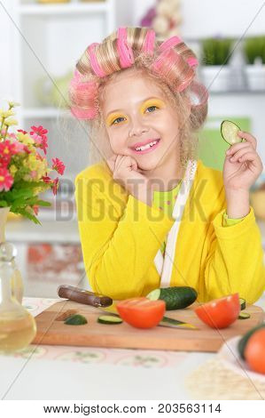 portrait of happy Little pretty girl   in hair curlers  sliced vegetables