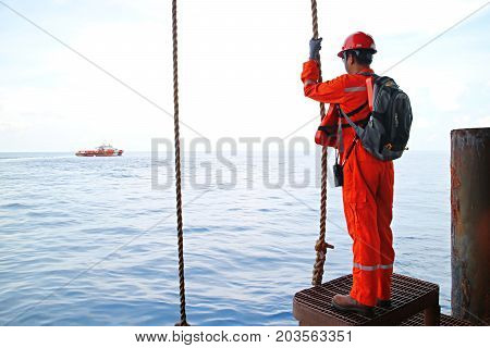 The worker prepare swing rope from platform to supply boat or passenger ship at oil and gas remote platform  for working at the wellhead platform or remote platform.