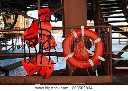 Life buoy and work vest or life vest hanging on the handrail of offshore platform oil and gas.