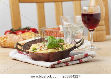 closeup of spaghetti carbonara with wine on a table