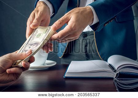 Man Businessman In Suit Takes The Money Hands. A Bribe In The Form Of Dollar Bills. Concept Of Corru