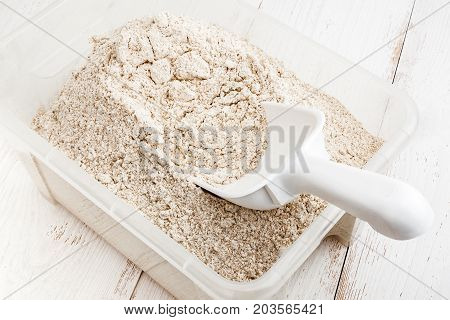 Plastic container with healthy wholegrain flour close-up