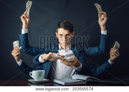 Businessman With Six Hands In Suit Holding Money In The Form Of Hundred Dollar Bills. Concept Of Cor