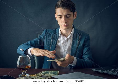 Businessman In Suit Throwing Money In The Form Of Hundred Dollar Bills. Concept Of Investments And S