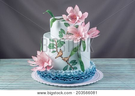 A Beautiful Home Wedding Three-tiered Cake Decorated With Pink Flowers And Branches With Green Leave