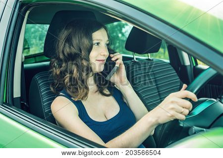 Woman driver talking on a cell phone in the car. Distracted and dangerous driving. The traffic violation. poster