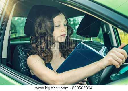 Woman Driver Reading A Book In The Car. Distracted And Dangerous Driving. The Traffic Violation.