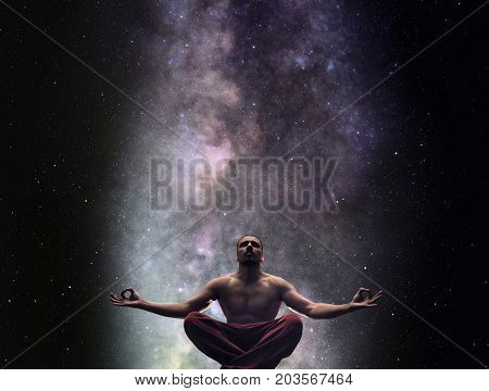 Meditating man against Milky Way and the stars