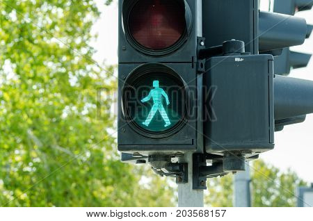 Green traffic light for pedestrians on the crosswalk