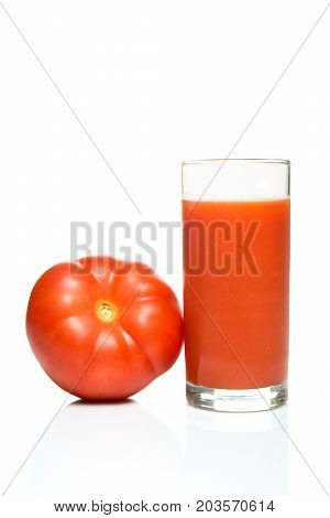 Glass of tomato juice with tomato fruit and reflection isolated on white background