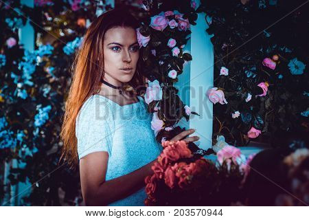 Young woman staying in front of her beautiful flower house