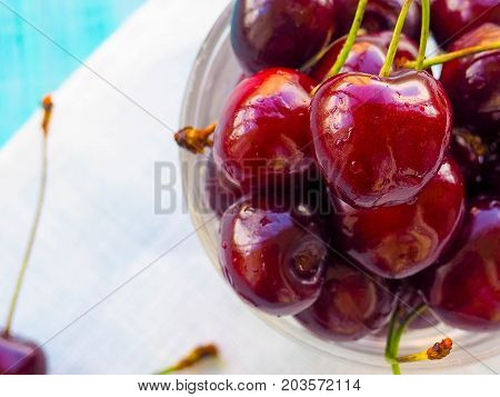 Fresh cherry on plate on wooden blue background. fresh ripe cherries. sweet cherries. Cherries in color bowl and kitchen napkin. Red cherry. Cherry on white background. healthy food concept. Flat lay