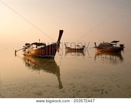 Local long tail boat in sea at sunrise when tide is falling or going out. Peaceful feeling at Lipe Island Satun Thailand.
