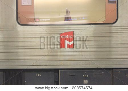 LISBON, PORTUGAL - JUNE 7, 2017: Lisbon Metro small red square logo on empty train car background. Modern metropolitan transit point underground view. Opened in 1959, first metro system in Portugal.