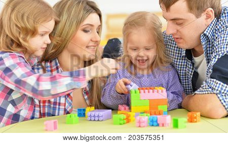 Portrait of a parents playing with adorable little daughters