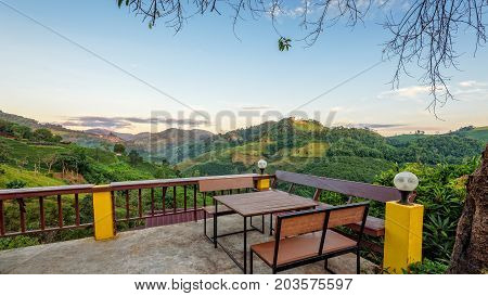 Table and chairs on the terrace for dining and enjoy the beautiful natural landscape of forest and mountains in the morning atmosphere at Doi Mae Salong view point in Chiang Rai Province Thailand