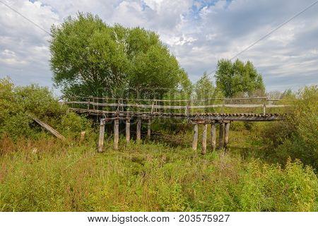 old wooden broken bridge across a ravine