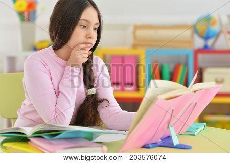 Portrait of a schoolgirl doing homework in her room