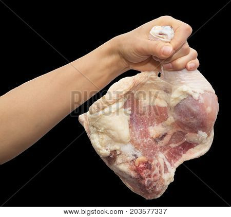 chicken leg in hand on a black background