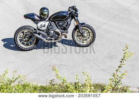 Cool looking custom made scrambler style cafe racer with helmet standing on road