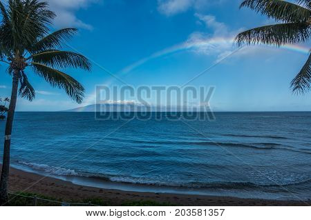 A view of a rainbow over the ocean in Maui Hawaii.