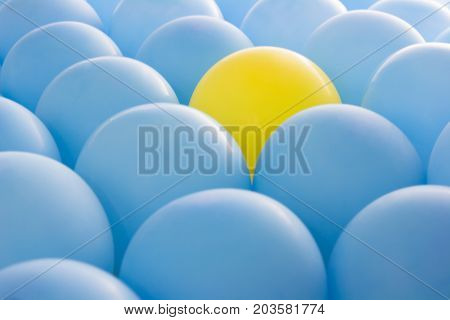 Different concept , One yellow balloon in blue balloons.