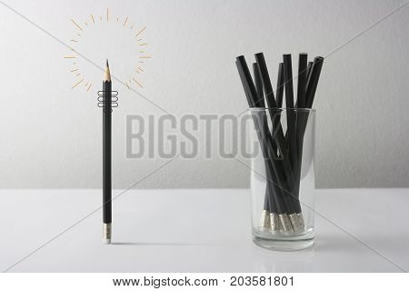 Individuality symbol and independent thinker concept and new leadership concept or individuality as a group of Pencil on white paper with one individual in the opposite direction as a business icon.