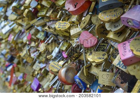 PARIS FRANCE - AUGUST 26 2017: Tourists from around the world visit Paris and bind their love buying a lock on which they write their names and then throw the key into the Seine River.