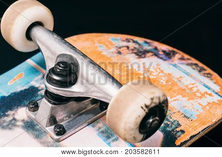 Skateboard parts on black background, rubbed deck and wheels on truck. Professional extreme sport and skateboarding elements, close up picture poster