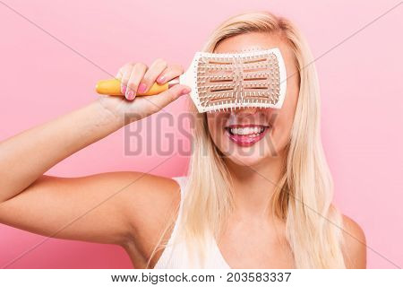 Beautiful woman holding a hairbrush on solid background