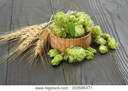 Beer Brewing Ingredients Hop Cones In Wooden Bowl And Wheat Ears On Dark Wooden Background. Beer Bre