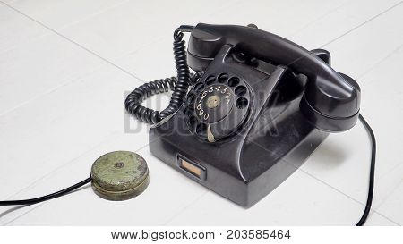 Telephone antique black color Isolate on white wood floor has copy space.