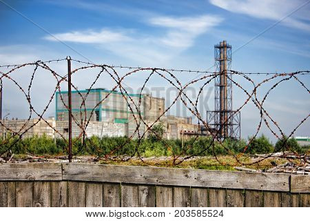 Restricted area - wooden fence with barbed wire plant in the background