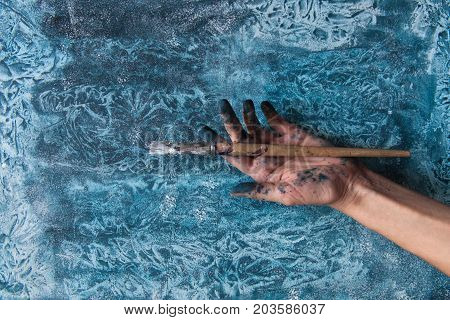 Dirty Female Hand With Paintbrush On Background Of Colorful Background. Creativity Drawing Concept.