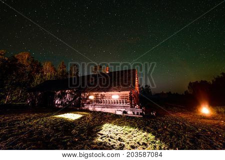 The Milky Way In Night Sky With Stars Over Wooden Country House At Night
