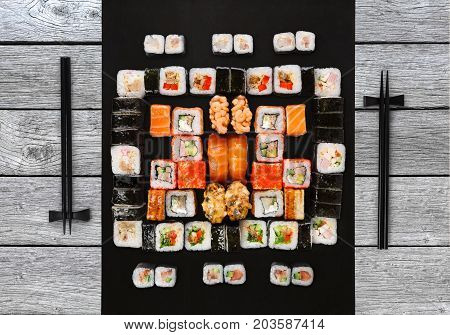Japanese food restaurant delivery - sushi maki, unagi, gunkan and roll big party platter set on gray wood background, above view