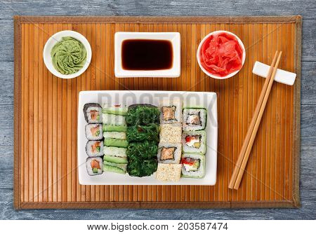 Japanese food restaurant delivery - sushi maki, unagi and roll platter set on mat on blue wood background, above view