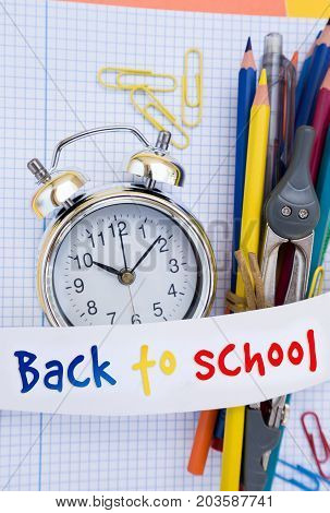 back to school concept - alarm clock and school supplies close up with back to school text on paper ribbon