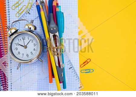 back to school concept - alarm clock and school supplies close up border with copy space