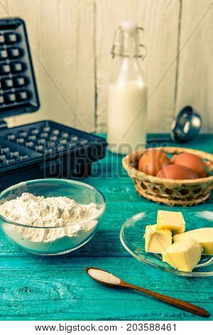 Making waffles at home - waffle iron and ingredients - milk, eggs and flour. Cooking background.
