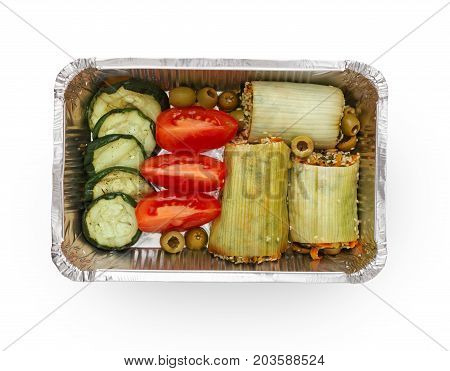 Healthy lunch in foil container. Healthy food take away and delivery. Zuccini stuffed with rice, cuted tomatoes, cucumber and olives in box on white background, closeup, isolated